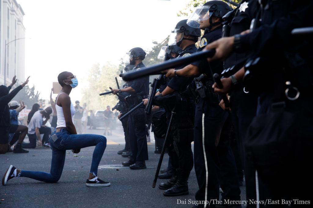 ΗΠΑ: Η φωτογραφία με τη μαύρη διαδηλώτρια που γονατίζει μπροστά στους αστυνομικούς και έγινε viral